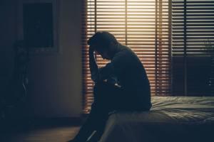暗い部屋の中で頭を抱える男性