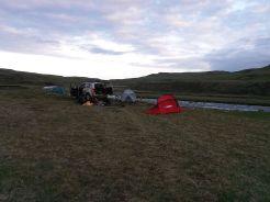 Az óceán partjáról a Vatnajökull óriásgleccser közelében levő Laki településhez próbálunk feljutni az F206-os úton. Abban reménykedünk: ha korábban lezárt út miatt (ezeket használhatóságát nagyon ajánlott előre ellenőrizni a www.road.is weboldalon!) képtelenek voltunk feljutni a Hekla tűzhányó közelébe, legalább most jussunk fel egy extrém helyre a bérelt terepjárónkkal. Bár nehézkesen ugyan, de sikerült volna átjutnunk a folyón, odébb az út le volt zárva. Annak ellenére, hogy tudtuk: az izlandiak számára a legnagyobb sértést az jelenti, ha a turisták elhagyják terepjárójukkal az aszfalt vagy makadám utat, itthoni mentalitás szerint az út és a patak között parkoltunk a zöldövezetben. A szabályokat feledtették velünk a körülmények: hosszú nap, egy szép sátorhely megtalálása és a néhány (bár a reptéri vámmentes üzletben vásároltuk, mégis méregdrága) sör. A patakban történt reggeli mosakodást és a sátorozást talán még elnézte volna nekünk, de a hirtelen felbukkanó, valamely nemzeti park feliratával ellátott kocsiból kiszálló morcos férfi azonnal lefényképezte a járművet, s mielőtt elviharzott volna azt mondta: 3000 (igen, háromezer) euróig terjedő büntetést kaphatunk. Belénk fagyott a vér. Hiába mondtuk, hogy amennyiben az úton hagyjuk a terepjárót, senki sem tud elhaladni mellettünk, a férfi hajthatatlan maradt. Minden valószínűség szerint az intézmény elkéri a kocsit bérlő személy adatait a cégtől, s kiállítják a büntetést. Hátha mégsem jön boríték Izlandról...