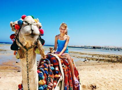 Tourists-children-riding-camel-on-the-beach-of-Egypt.-Sharpness-on-a-camel._shutterstock_144340636