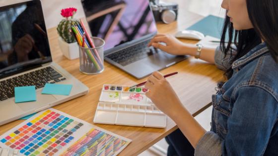 机に座って水彩絵の具で絵を描こうとしている女性の画像