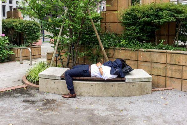 ベンチの上で仰向けになるスーツ姿の男性