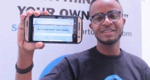 Adam A. Duma, cofondateur de Smartclass, une plate-forme d'apprentissage en ligne, présente la vue mobile de Smartclass lors d'une interview. Photographie de Goodhope Amani, reproduite avec autorisation.