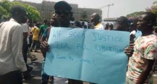 Un manifestant pose pour une photo sous la bannière « Save the State », photo de Mark N. Mengonfia, 7 juin 2019, Monrovia, Liberia, utilisée avec permission.