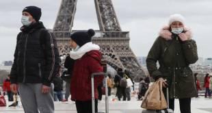 Plusieurs personnes devant la Tour Eiffel, le 12 Mars 2020.