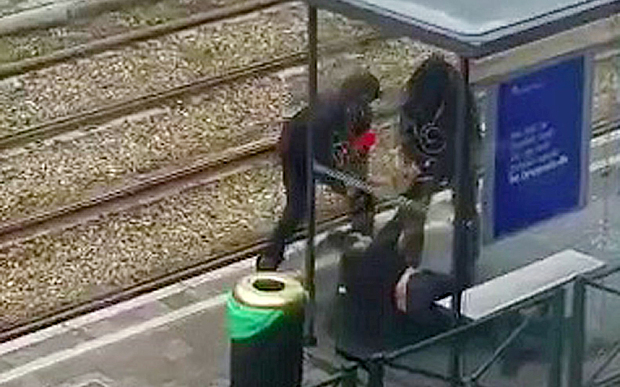 Belgian police drag a suspect along a tramway platform, in this still image taken from amateur video, after the suspect was shot, in the Brussels borough of Schaerbeek, following Tuesday's bombings in Brussels, Belgium