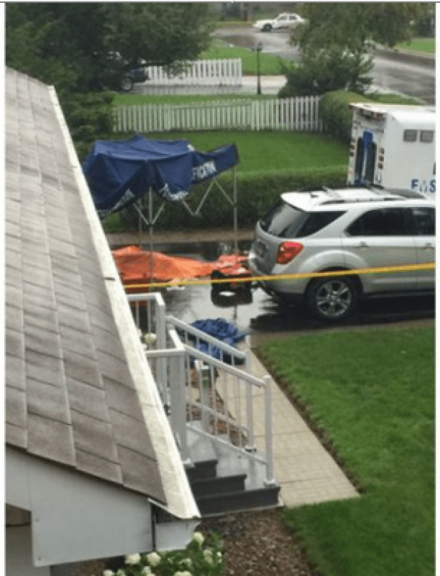 A body lies covered in front of a house1.png