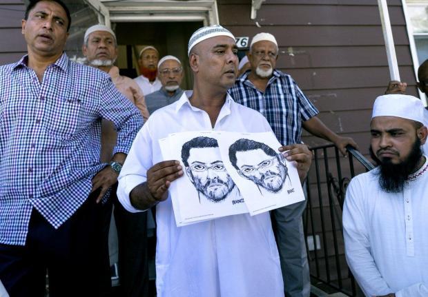 Members of Al-Furqan Jame Mosque show a sketch of the suspect.jpg