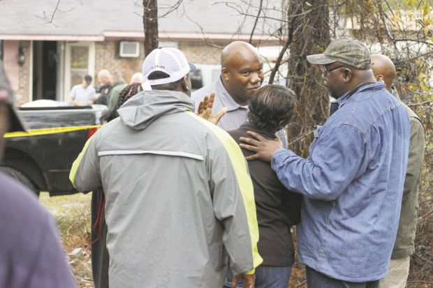 LeCarious Oliver, center, with the Mississippi Bureau of Investigation, speaks with family members in front of a home on Butts Road in Toomsuba where four family members were found shot.jpg