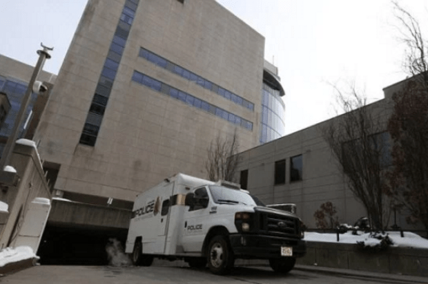'Changing times' Karim Baratov leaves court in Ontario, Canada on Wednesday in a police paddy wagon.png