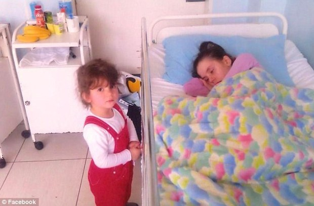 : Danijela's daughter, Marija, is seen looking puzzled by her mother's bedside.jpg