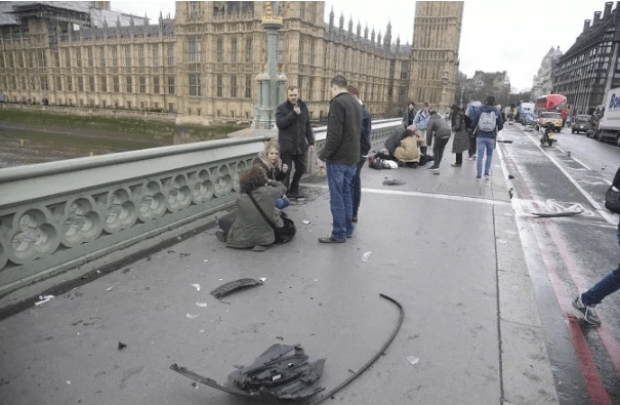 Pieces of a vehicle's undercarriage scattered on the pavement of Westminster Bridge as the public went to the aid of victims.png