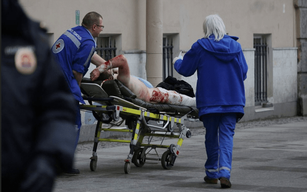 An injured passenger is helped by emergency services outside Sennaya Ploshchad metro station, following explosions in two train carriages at metro stations in St. Petersburg, Russia April 3, 2017.png