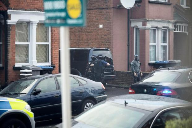 Armed cops swooped on the property with a woman shot as suspects were apprehended.jpg