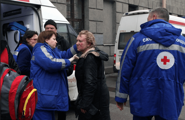 EMTs attend an injured woman outside Technological Institute metro station in Saint Petersburg.png