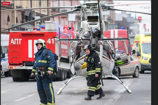 First responders, EMTs and Firefighters survey the carnage with a backdrop of emergency service vehicles and a helicopter near Tekhnologichesky Institut station of the St Petersburg met