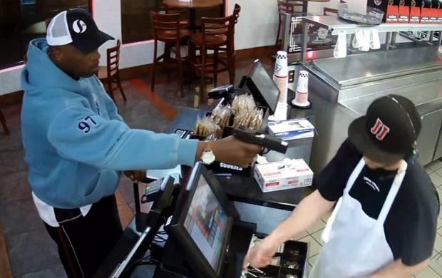 The man wearing a light blue hooded sweatshirt entered the restaurant, placed an order, then pulled a gun instead of a wallet out of his pocket and pointed it at the cashier.jpg