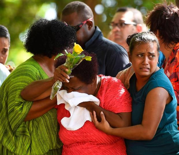 Thaiday's relatives comfort one another after she murdered eight children in the family