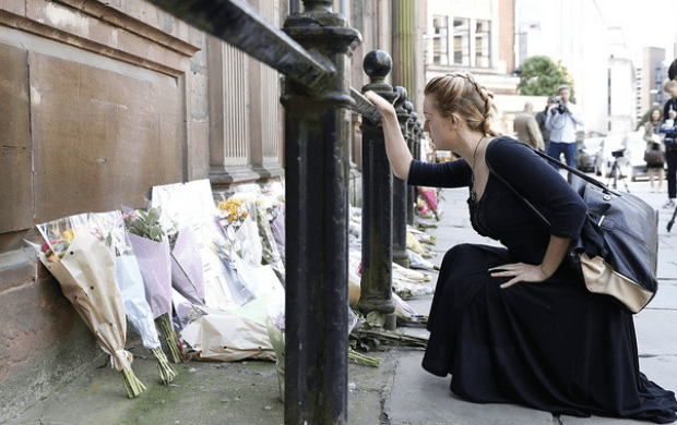 Woman pays homage at memorial set up in memory of a horrific attack that has left Manchester in shock.png