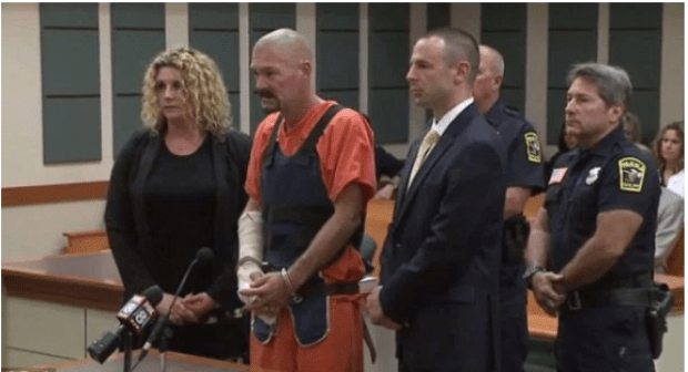 Brinkman is arraigned for his bail hearing wearing a cast on his hand.png