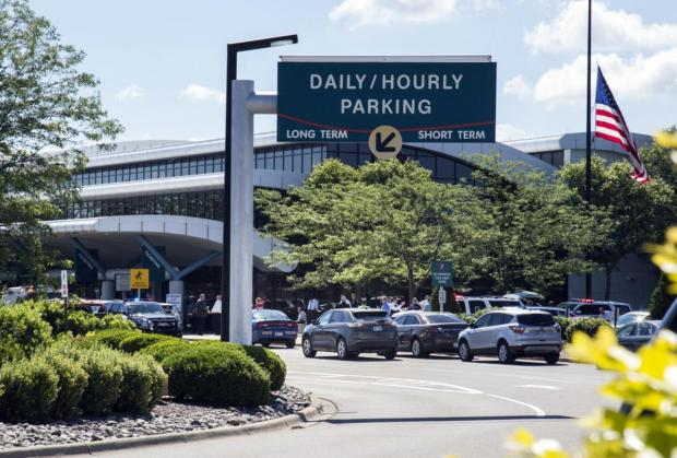 Delays as stranded travelers sit outside a terminal at Bishop International Airport following Wednesday's attack on a police officer by a suspected terrorist.JPG