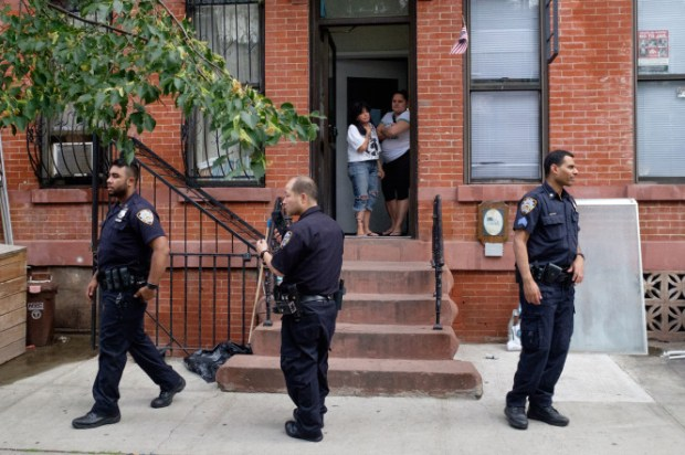NYPD officers stand outside the apartment where the 20-year-old malewas stabbed and beaten with bats in Brooklyn early Monday..jpg