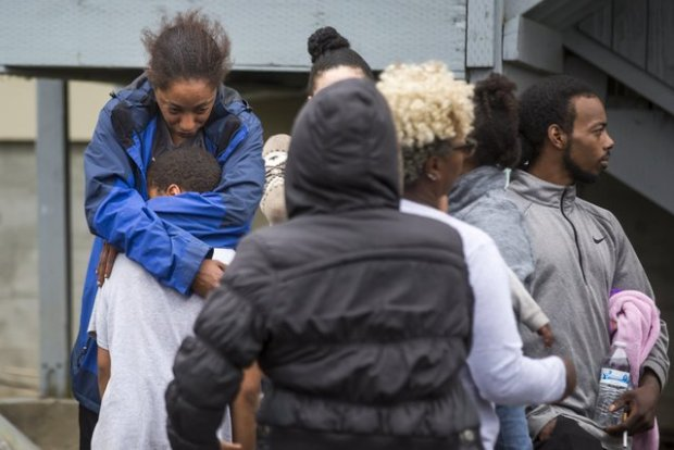 Victim's sister Monika Williams cradles one of the children on the scene, as family members gather, after police fatally shot her sister .jpg