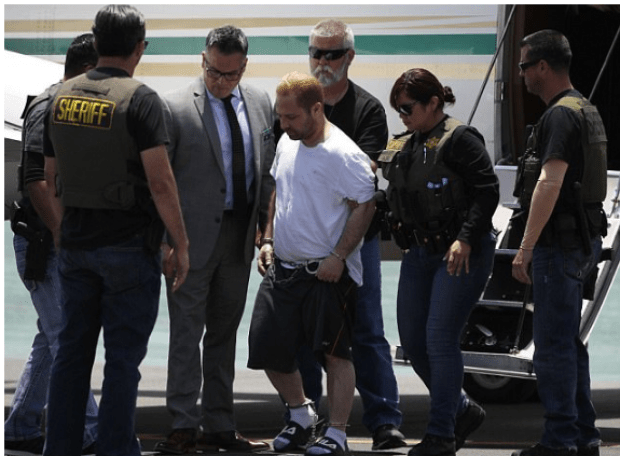 Andressian is escorted off a plane in shackles after landing at the Long Beach Airport on Friday.png