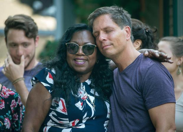 Don Damond, the fiancé of Justine Damond, is comforted outside his home by Valerie Castile1 sister of police shooting victim, Fenando Castille.jpg