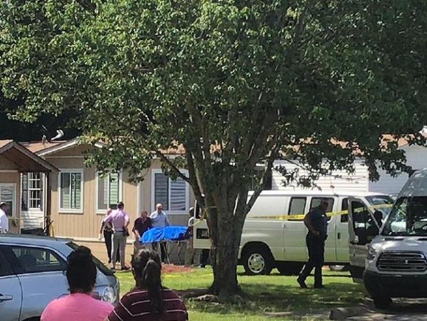 EMTs in Gwinnett load a body into a crime scene vehicle..jpg