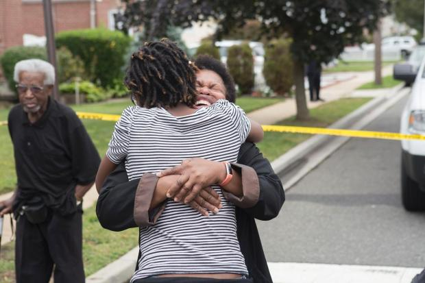 Loved ones of Lynn Reuchenbach-Vanderhall, Melissa Vanderhall and family friend Janel Simpson cry Saturday outside the scene of their slaying in Hempstead, Long Island.jpg