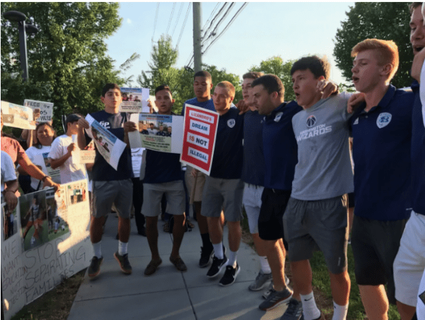 Members of Lizandro Claros Saravia's Bethesda Soccer Club team chant at a rally Monday protesting his planned deportation.png