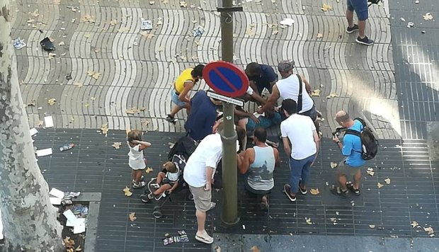 People gather round a victim after the van drove into a crowd in Barcelona .jpg