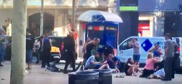 People sit on the pavement in Barcelona after a van ploughed through pedestrians in Las Ramblas.jpg