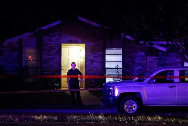 officer investigates after a shooting at a home in Plano, north of Dallas, Tex., Sunday night