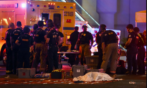 Las Vegas EMTs and police triage as a body lies under a sheet after Sunday night's shooting in Las Vegas 5