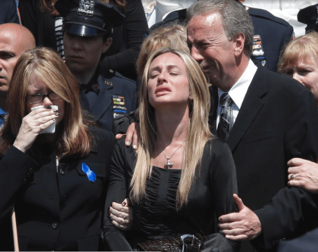 Brian Moore's mother Irene, left, sister Christine, center, and father Raymond at his funeral 1.png