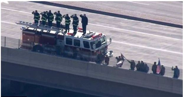 Members of the fire department salute as the motorcade drives by 1