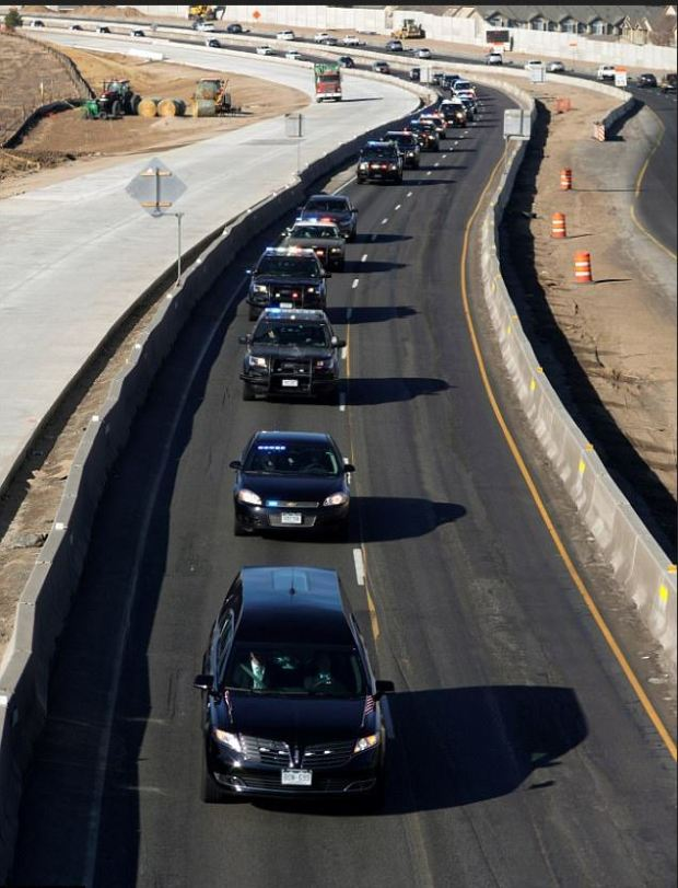 Police vehicles escort the hearse carrying the body of Parrish, who was killed on Sunday morning..JPG