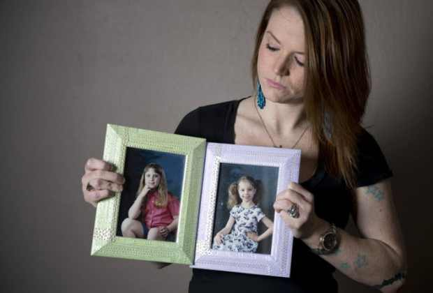 Christie Battaglia, surviving daughter of John Battaglia, holds up photos of her two half-sisters, Faith (left) and Liberty. .jpg