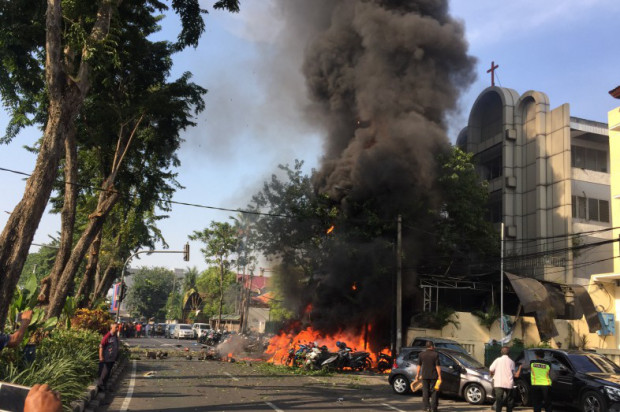 Motorcycles burn following a blast at the Pentecost Church Central Surabaya.jpg