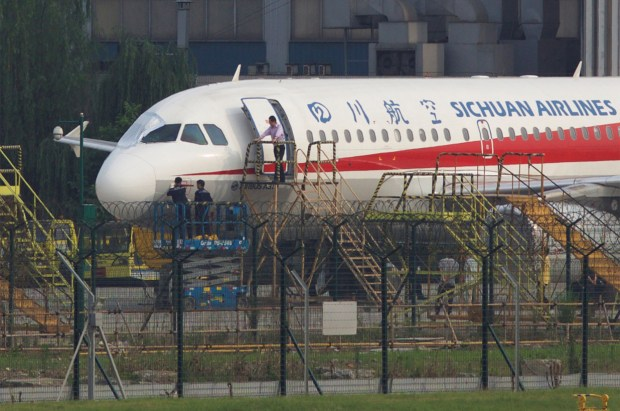 Workers inspect Airbus after Flight 3U8633, of China's Sichuan Airlines, made an emergency landing on Monday.jpg