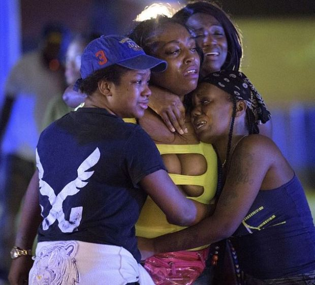 Members of affected family weep and comfort each other 1.JPG