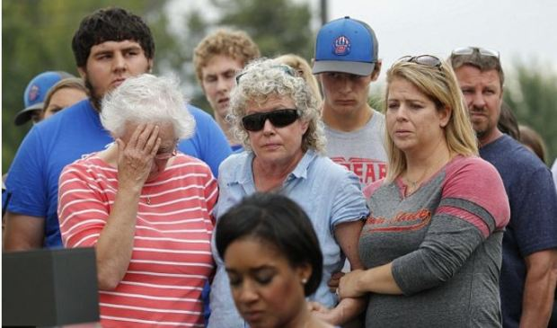 Mollie Tbbetts mother  Laura Calderwood [center], in blue and brother Jake Tibbetts also in blue tee shirt.JPG