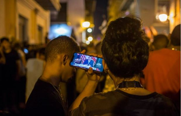 Puerto Ricans listen on a smart phone to the pre-recorded message Gov. Ricardo Rosselló announcing that he is resigning 3.JPG