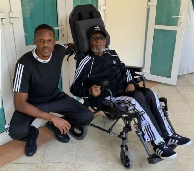 Robert Mugabe in a wheel chair with son Robert Mugabe Jr 1