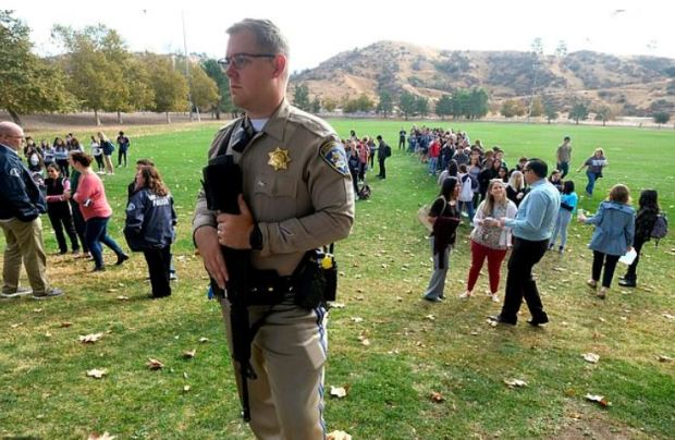 Police officer stands guard as students wait to reunite with their parents.JPG