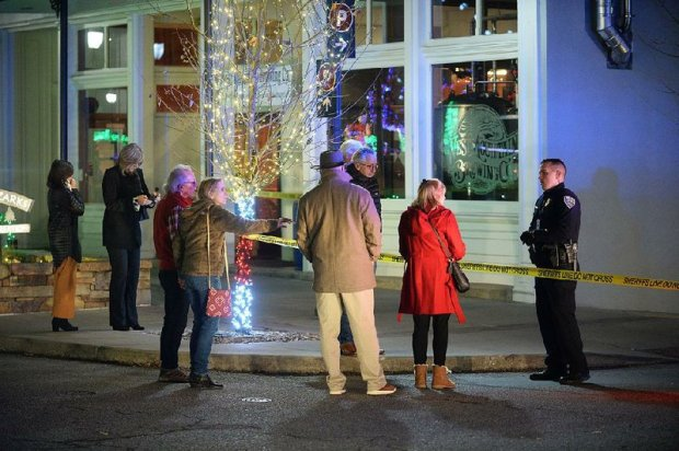 Bystanders ask a police officer about the shooting Saturday night outside the Fayetteville police station on Dec 7.jpg