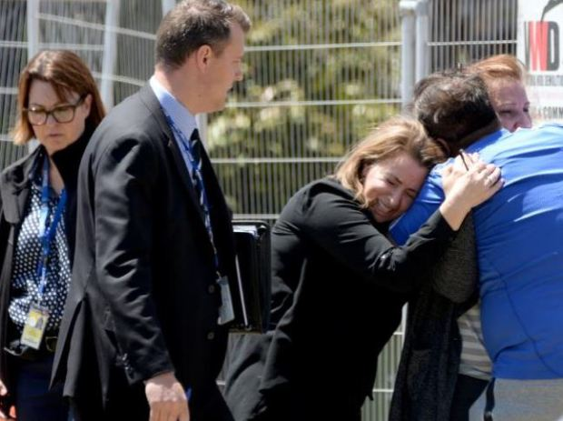 Friends or relatives embrace at the scene while police investigate the double shooting of Lindita and Veton Musai in their Melbourne home.JPG
