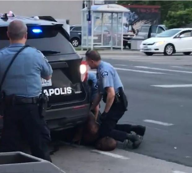White Minneapolis police officer pins a black man to the ground with his knees 9