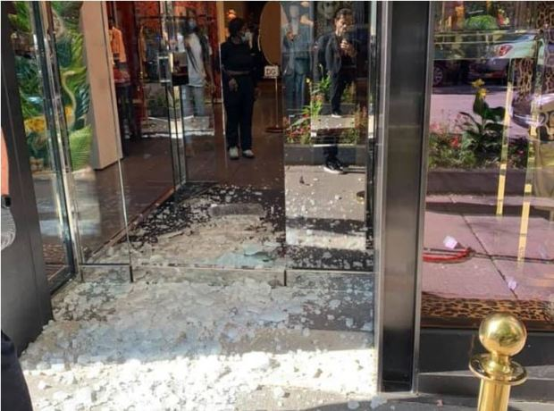 Shattered glass doors of one nearby shop after driveby shooting along Chicago's Magnificient Mile